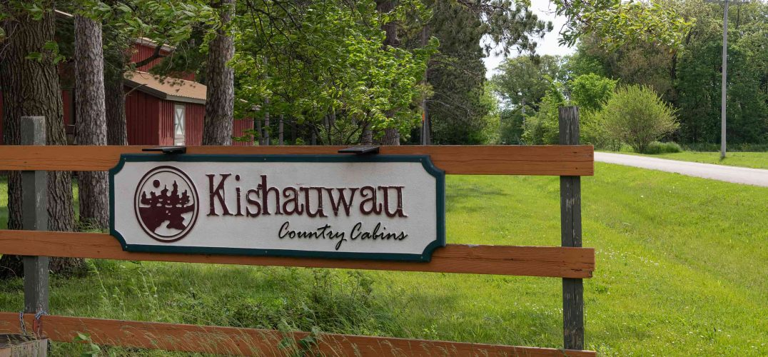 Entrance sign that says Kishauwau Country Cabins