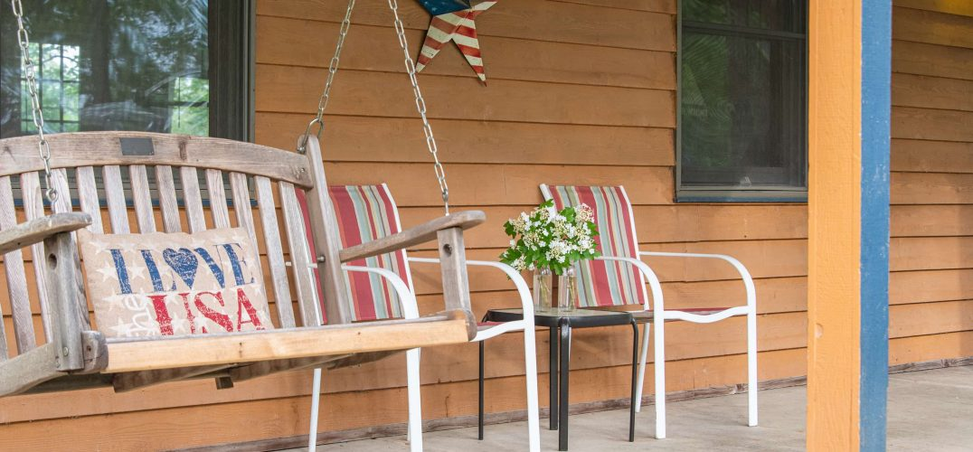 Front porch with porch swing and chairs decorated in red, white and blue