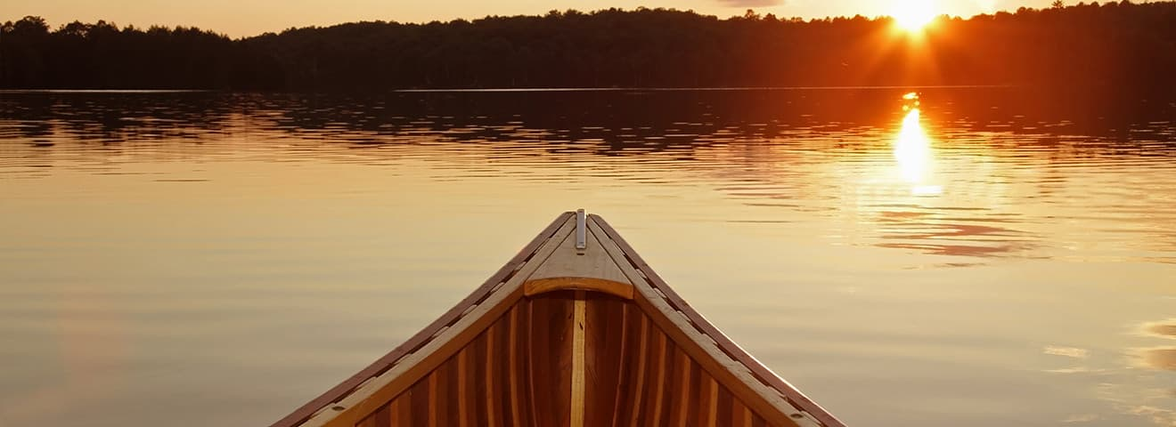 canoe on water at sunset