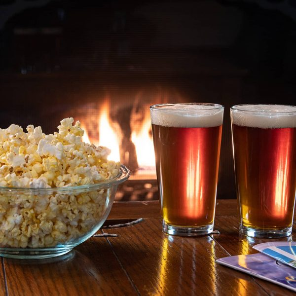 Popcorn and two beers in front of fireplace
