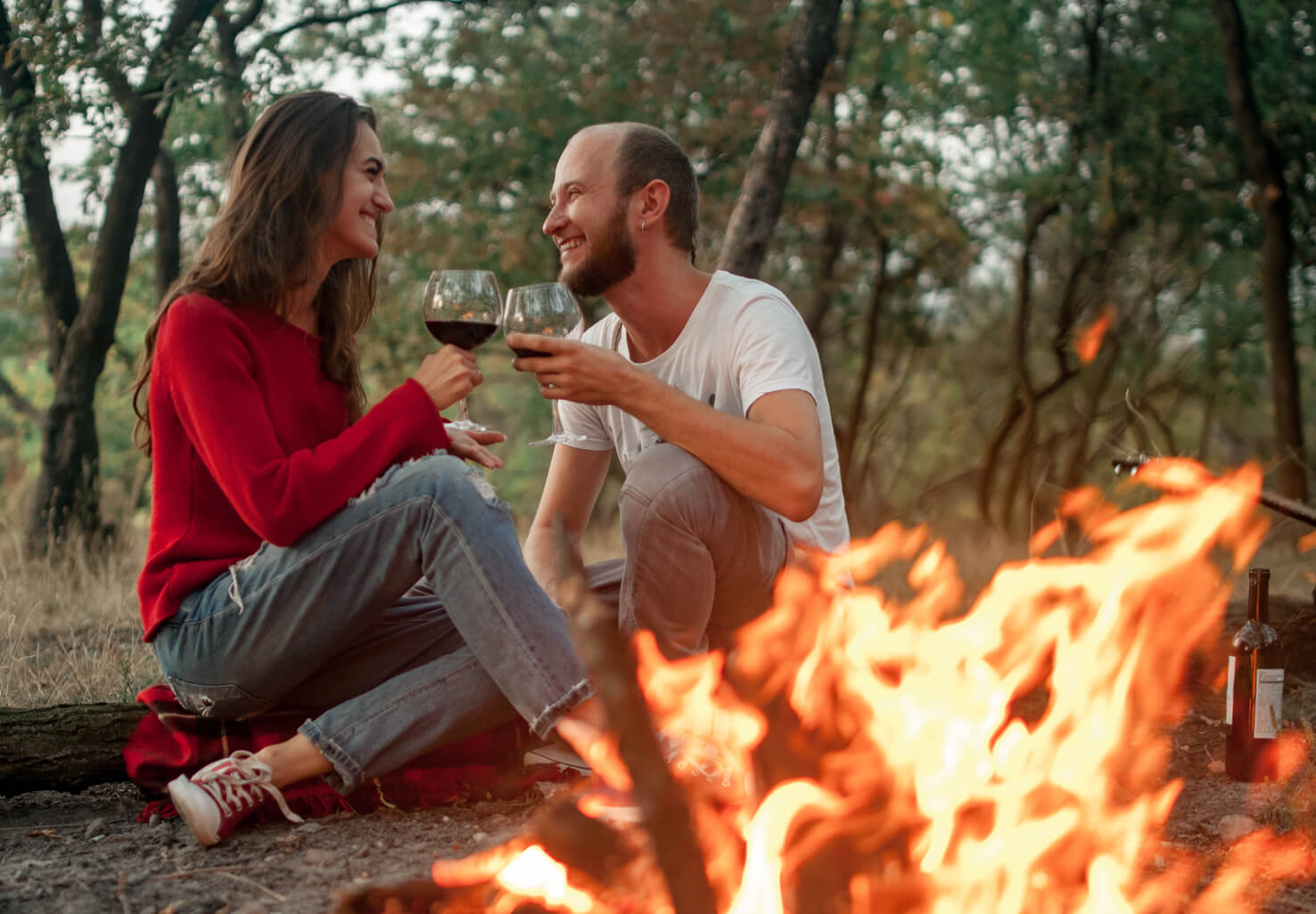 couple by campfire with wine glasses on Illinois honeymoon