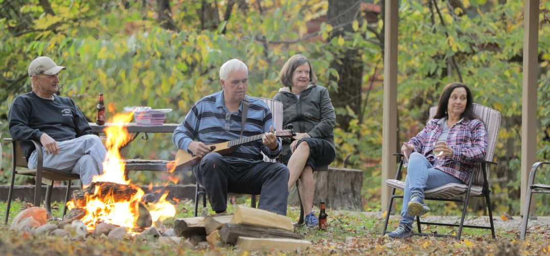 Family sitting around the campfire playing music