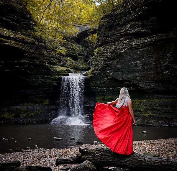 Woman in dress at a waterfall on a romantic Illinois cabin getaway