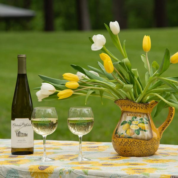Two glasses of white wine on Picnic table with flowers