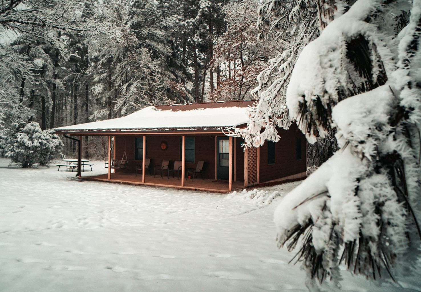 Exterior view of a cabin in winter with snow and icicles
