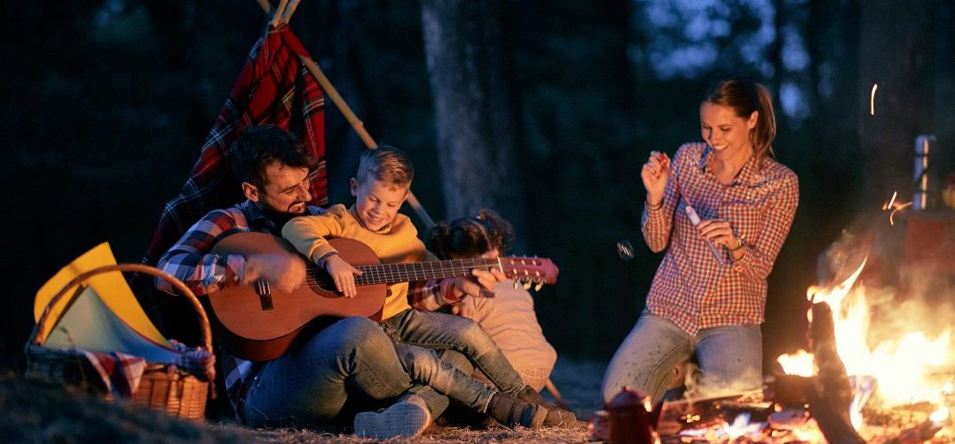 a family in the woods playing guitar by a campfire